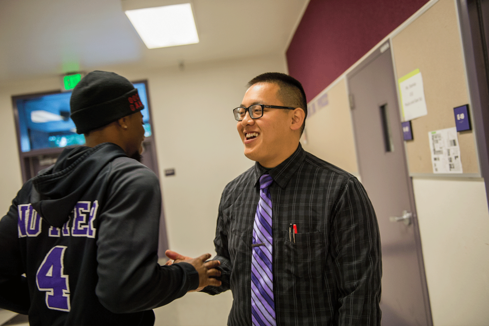 A young adult male in a black collared shirt, purple tie, and thick-rimmed glasses stands in a school hallway shaking the hand of a tall high school student in a black hat and black hooded sweatshirt.