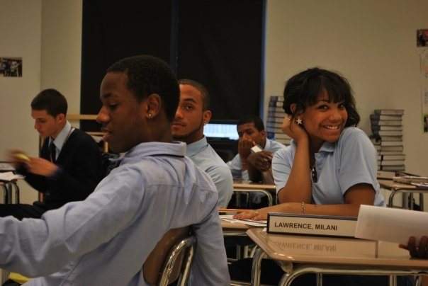 An older photo of a smiling high school female in a blue polo uniform shirt sitting in a classroom desk; three male students sit near her.