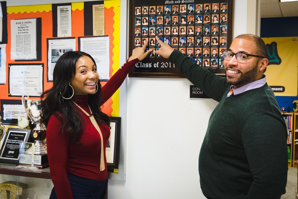 A young adult female in a maroon sweater and a middle-aged male in a green sweater and glasses stand next to each other, both are pointing at a framed class photo on the wall.