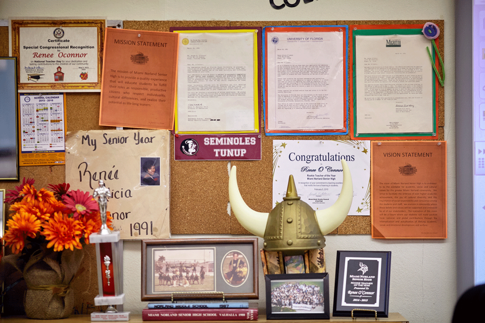 A bulletin board with several college acceptance letters and awards pinned to it; a trophy, viking hat, framed photos, and flowers sit on a shelf in front of the board.