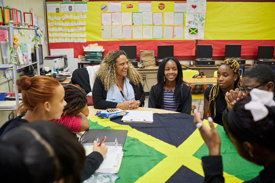 A group of high school students and teacher sit around a circular classroom table that has a bright Jamaican flag as it's table cloth; the teacher smiles while looking at a student.