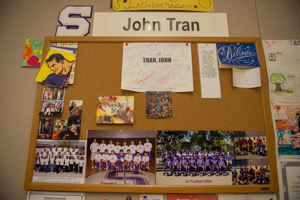 "A large bulletin board, with a sign reading ""John Tran"" over it; the board contains photos of student sports teams and yearbook photos."