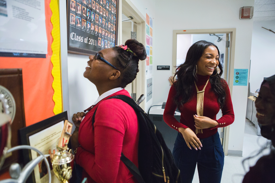 """A young adult female in a maroon sweater and long gold necklace stands at the front of a classroom smiling; in the foreground, a female student wearing a backpack stands looking up at a school class photo that says, """"Class of 2011"""" on it."""