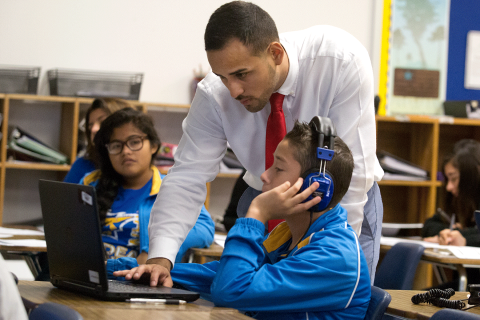 A young adult male teacher in a white collared shirt and tie stands over a young male student on a laptop with large headphones on; a couple of other students work at their desks in the background.