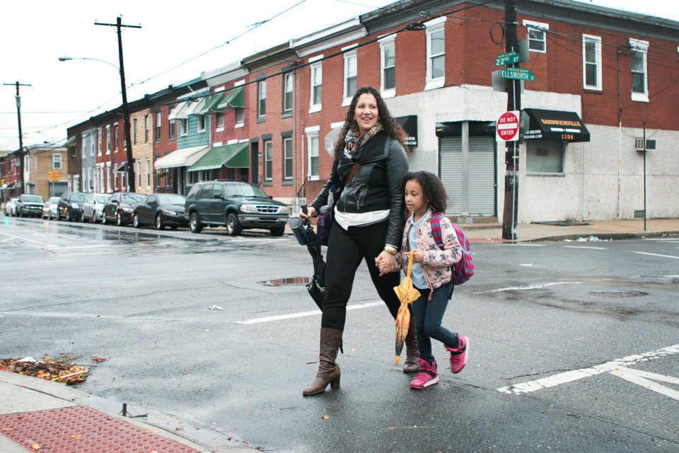 A young adult female holding an umbrella and coffee mug crosses a street with a young female wearing a jacket and backpack, also holding an umbrella; in the background are brick row homes and cars parked along the side of the street.