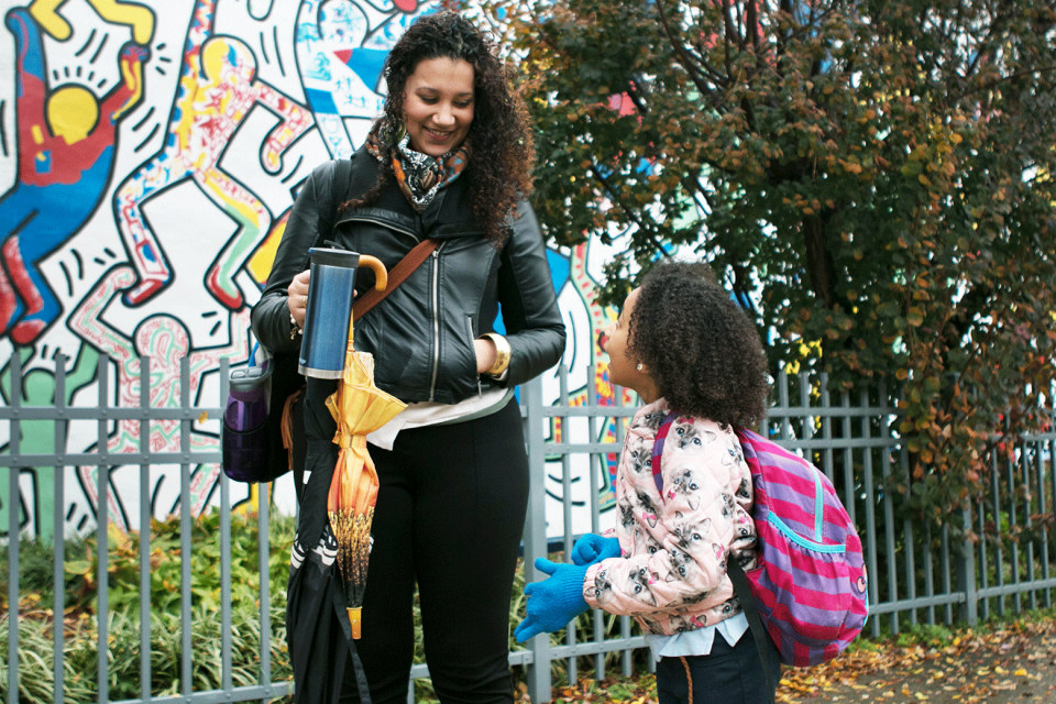A young adult female holding two umbrellas, a coffee mug, and a work bag, looks down at a young girl in a pink backpack who's talking to her; in the background is a metal fence and a colorful mural painted on a wall.