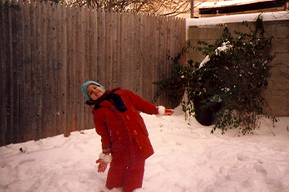 An older photographer of a smiling young girl in a red snowsuit and blue hat standing in a yard covered in a foot of snow, with a wooden fence behind her.