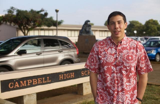 A young male teacher with short brown hair wearing a pink and white Hawaiian shirt stands in front of a parking lot and next to a sign that says Campbell High School.