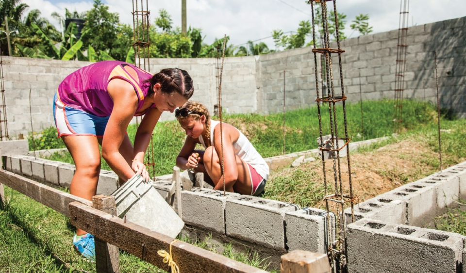 Two young adult females in shorts and tank tops lay cement between cinder blocks, forming the foundation for a new wall in a grassy area.