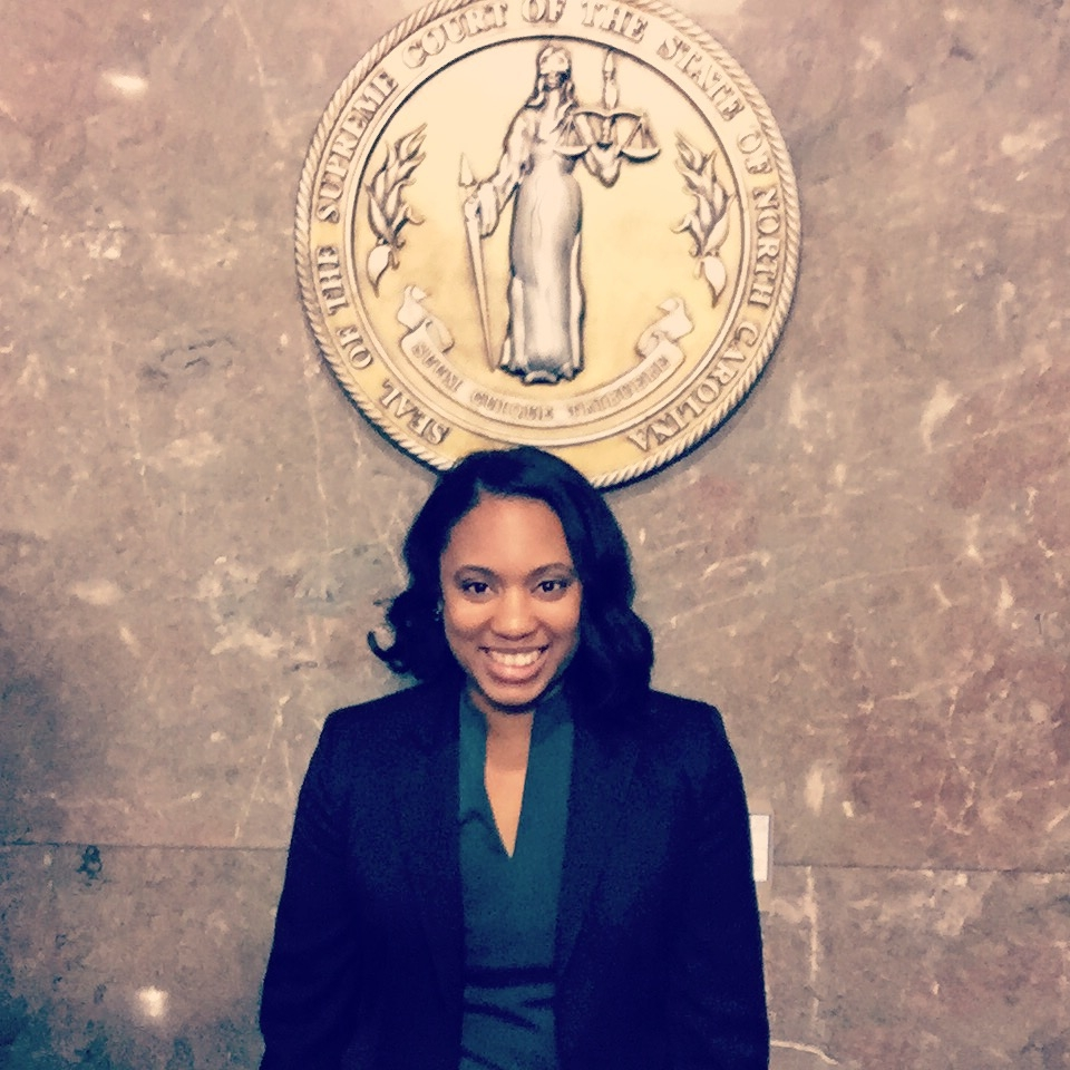A woman in a with black hair wearing a black blazer and green shirt smiles as she stands in front of the Seal of the Supreme Court of the State of North Carolina mounted on a marble wall.