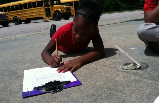 A school age girl with black braided hair wearing a red shirt and black pants lays on the pavement of a parking lot taking notes on a purple clip board with school buses in the sunny background.