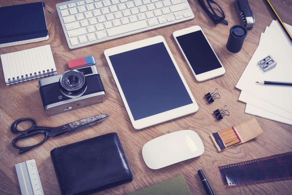 Image from above of a wooden desk with stationary, a camera, tablet, smartphone, glasses, wallet, and many other items.