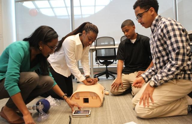 Four teenage students, two men and two women, are practicing First Aid training on the floor of a classroom using training tools and an iPad.
