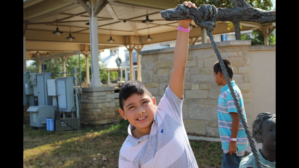 A middle school-aged boy with black hair hangs from part of a bronze statue, smiling.