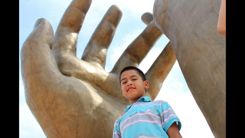 Low angle shot of a middle school-aged boy smiling under a statue of giant open hands.