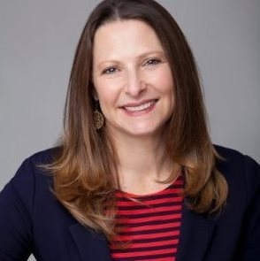 Headshot of a middle-aged female, in a navy and red striped shirt and navy blazer.