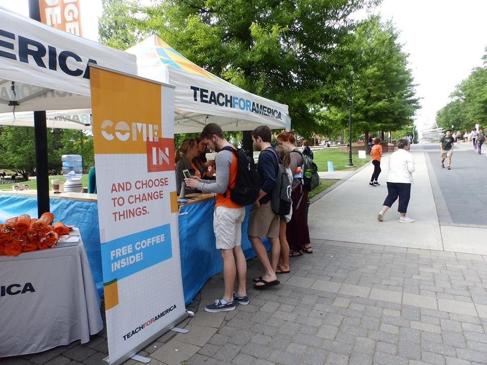 A group of college students gain information at a Teach for America information kiosk on a campus.
