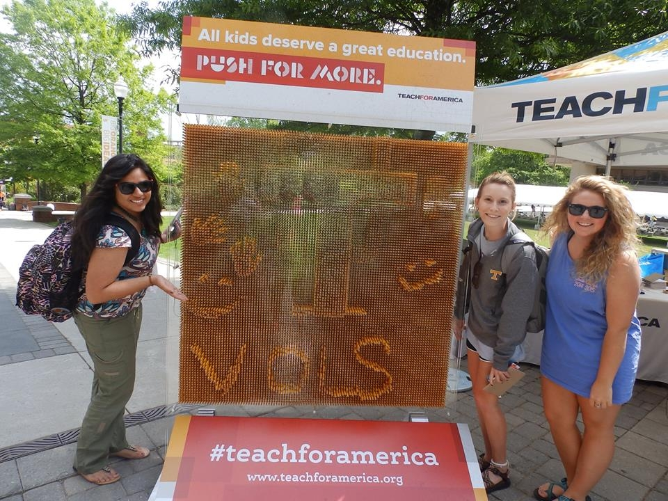 Three female college students posed around a Teach for America sign, smiling.