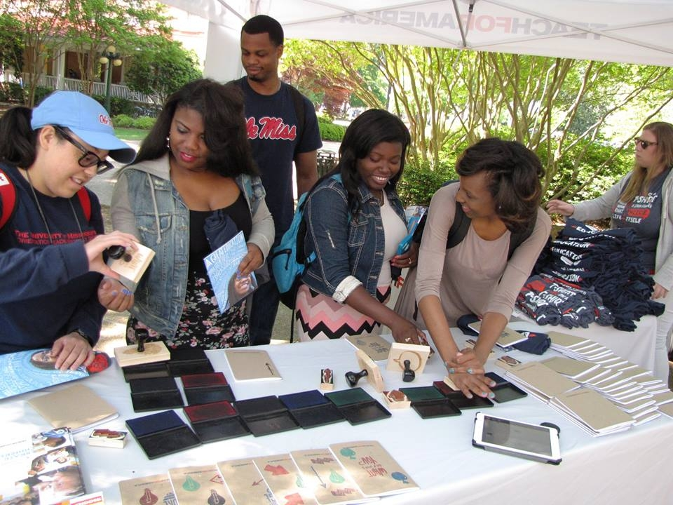 A group of college students playing with stamps at an outdoor TFA campus recruitment booth.