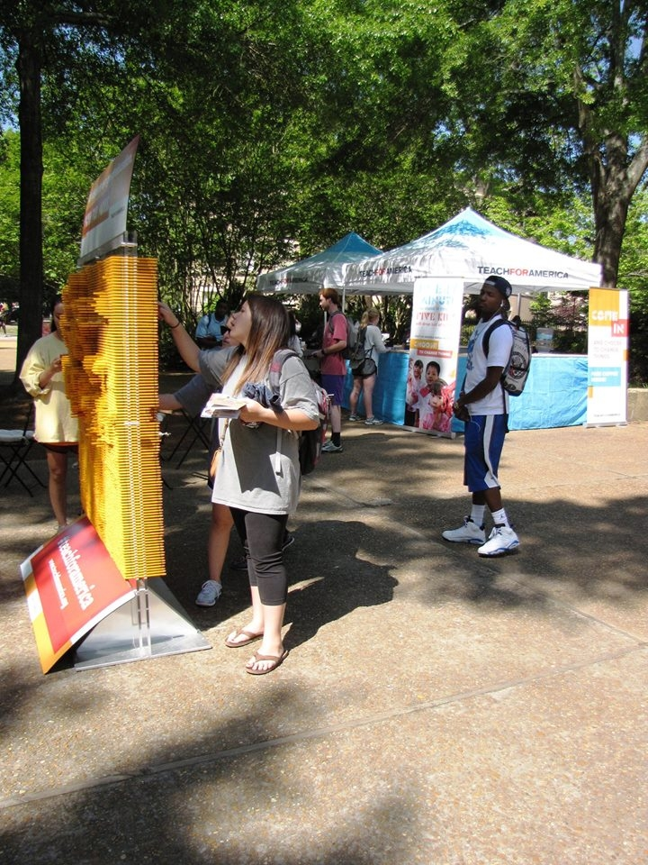 College students playing around a Teach for America sign at an outdoor recruitment booth.