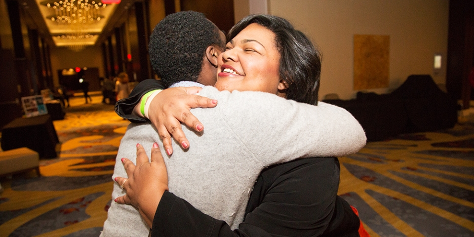 A woman in her thirties with black hair and a black shirt hugging a man with black hair and a grey shirt, in a hallway.