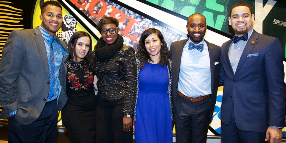 Three men and three women in thier thirties, wearng business attire, standing together in front of a very colorful mural, smiling.
