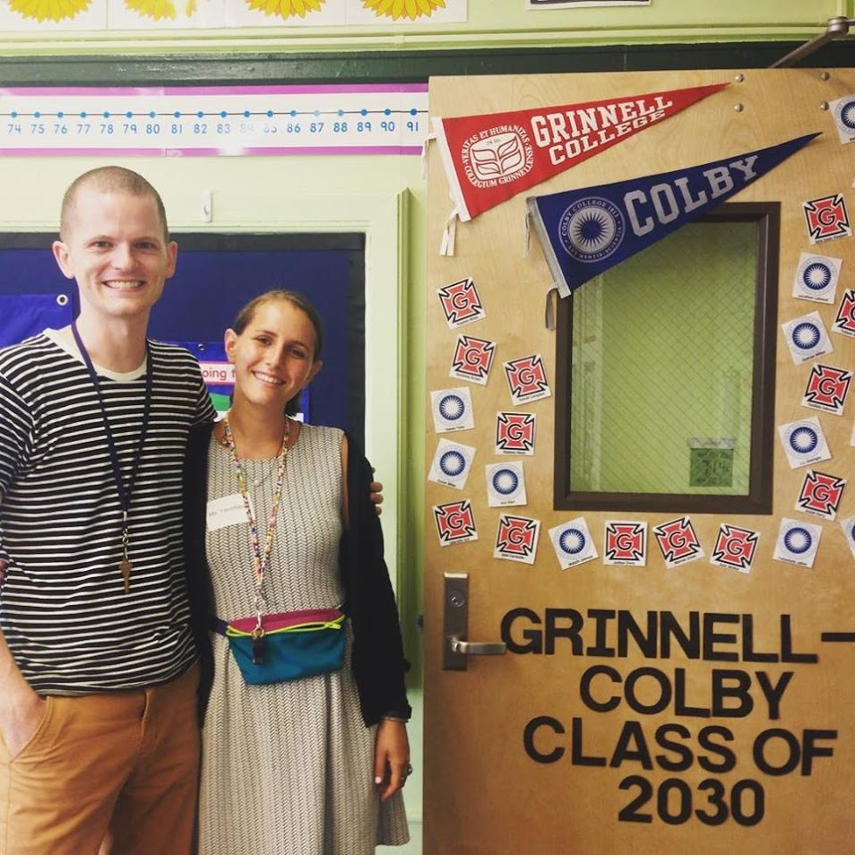 A tall man in his twenties, smiling, wearing a black and white striped shirt standing with his arm around a woman in her twenties wearing a grey dress and black sweater, next to an open door covered in flags and pictures, in a classroom.