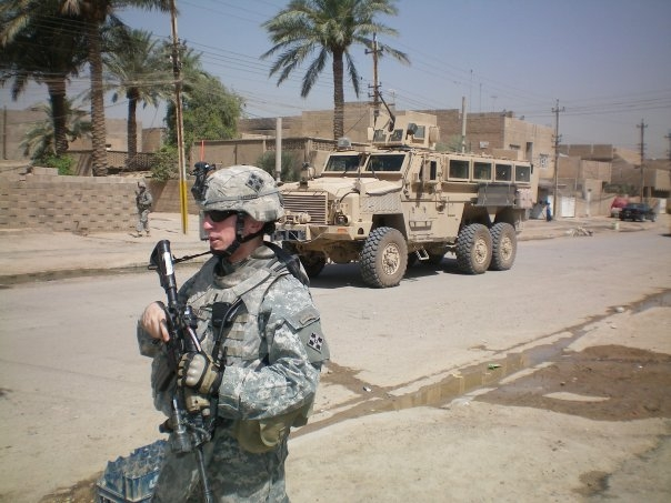 Soldier in front of military vehicle