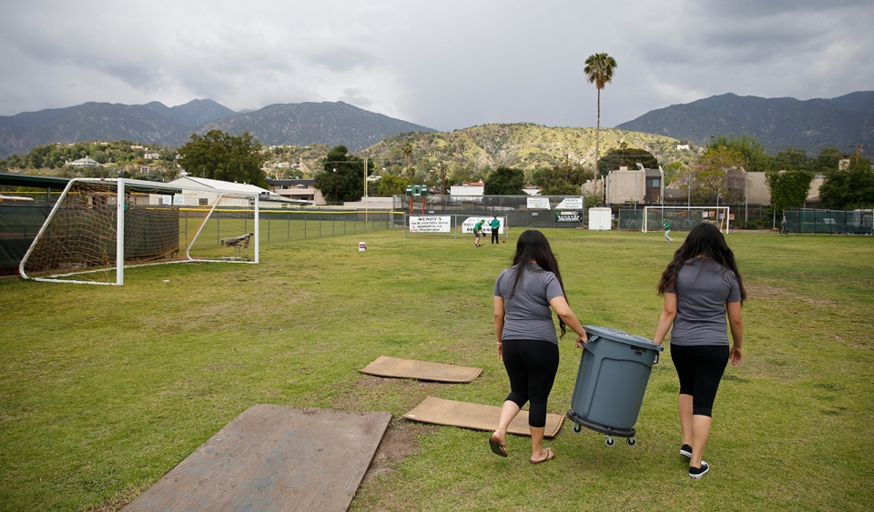 Two students walk across soccer field with a bucket.