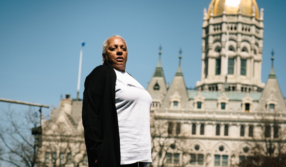 A woman standing in front of the the capitol building in Hartford.