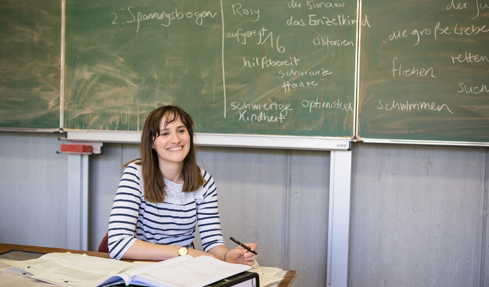 A teacher sits in front of a chalkboard.