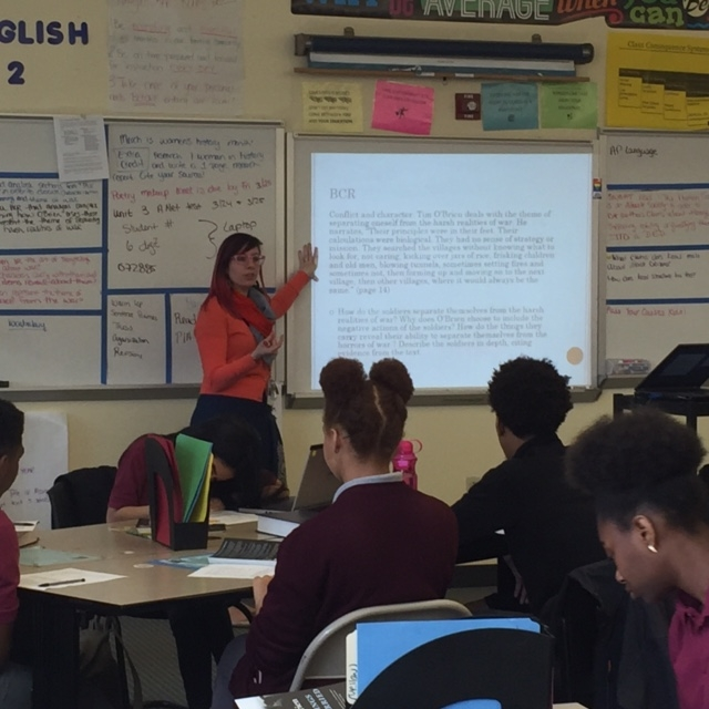 A woman in her twenties, wearing an orange shirt, teaching a class of middle school students.