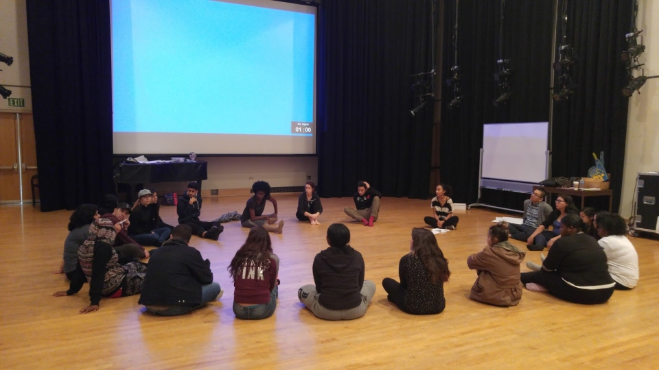 A group of high school students sitting in a circle on a hardwood floor, in a large room with stage lights, black curtains and a projector screen.