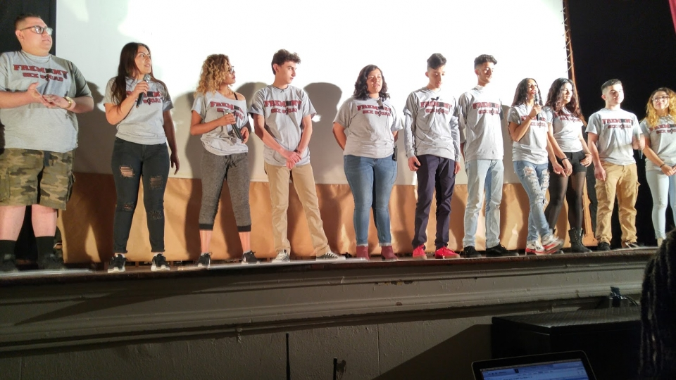 A group of high school students standing lined up across a stage holding microphones and wearing matching t shirts, in front of a projector screen.