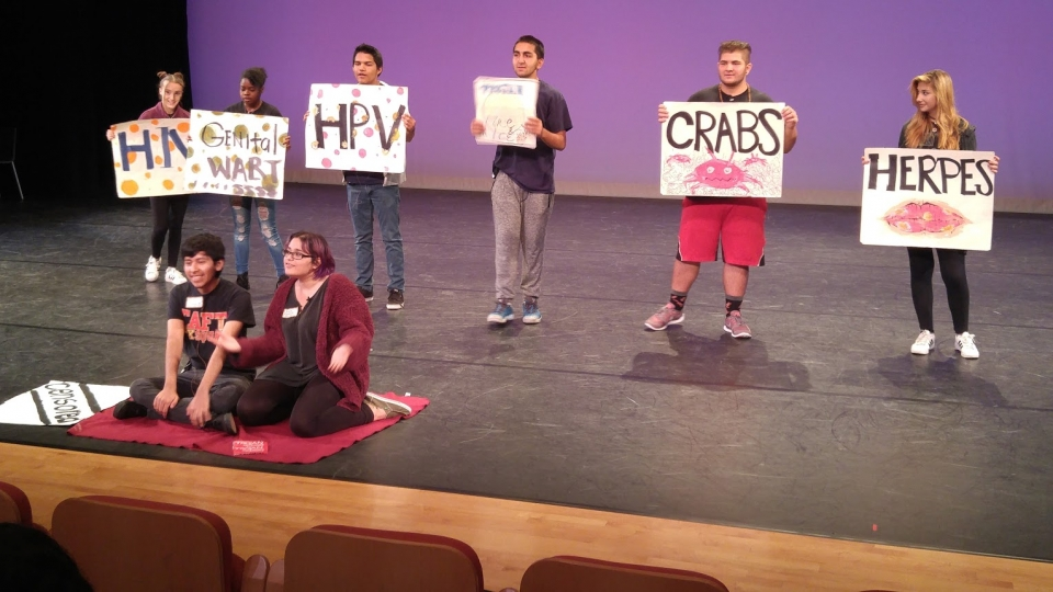 High school students rehearsing a sex ed presentation on a stage.