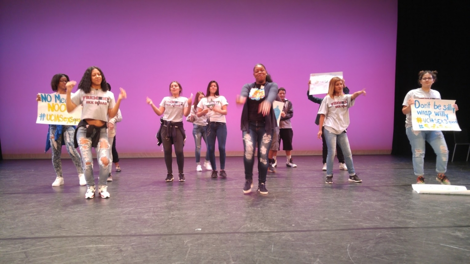 A group of a dozen high school students stand on a grey stage, some holding signs, performing a choreographed dance in front of a purple backdrop.