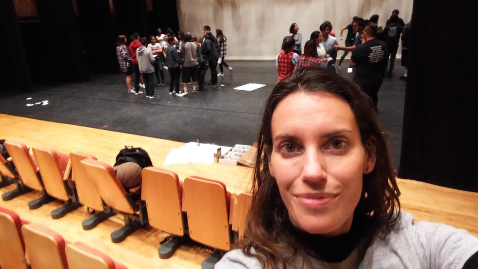 A woman in her twenties taking a selfie in front of a stage with groups of high school students standing in circles, having discussions.