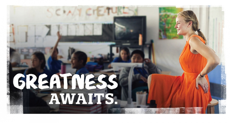 "A woman with long blonde hair, wearing an orange dress, sitting on a stool smiling at young students seated at desks in a classroom, with an overlaid title that states ""Greatness Awaits""."