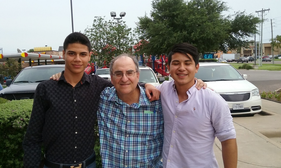 A middle aged man and two young men standing next to each other with arms on each others shoulders, smiling, in a parking lot in front of a playground.