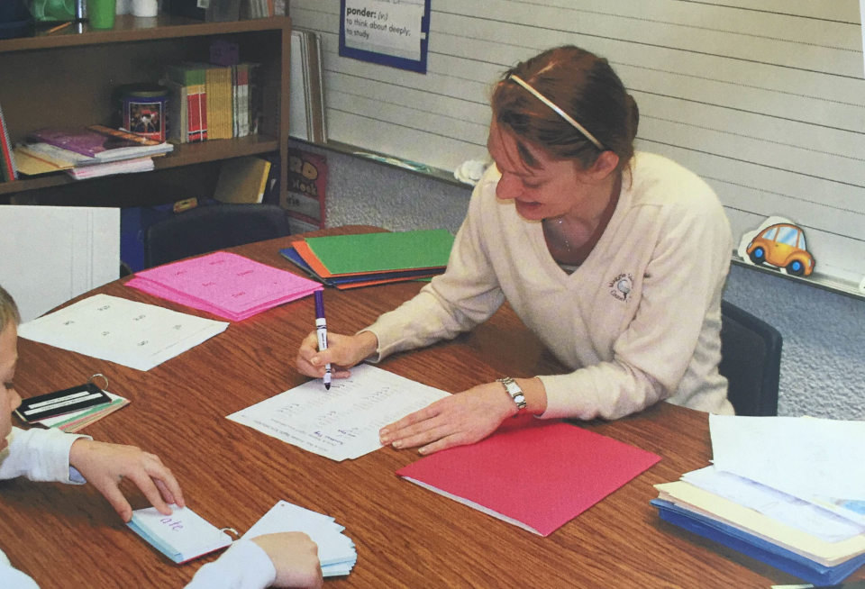 A woman in her thirties wearing a white sweater, making notes on a paper, white sitting at a desk across from a young student, in a classroom.