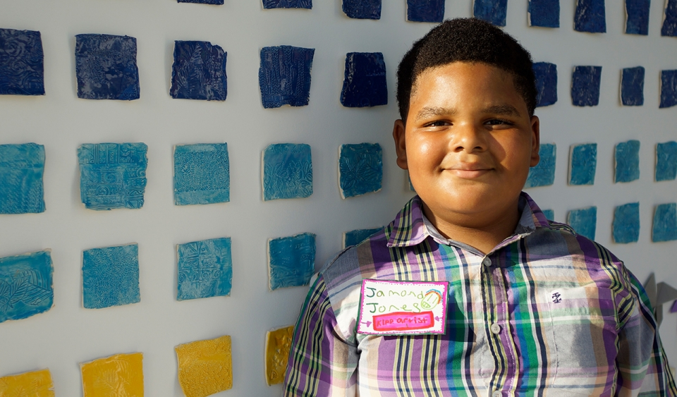 A young boy stands in front of an art exhibit
