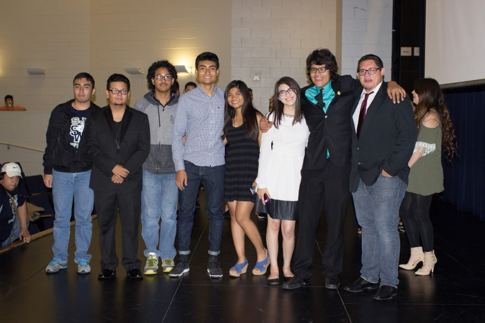 Group shot of well-dressed young men and women standing in a hallway.