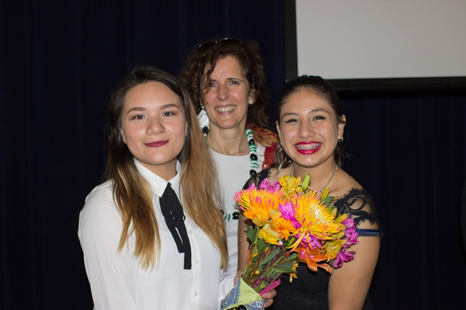 Two young women, one holding a bouquet of flowers, and a middle aged woman stand together, smiling, in front of a dark blue stage curtain and a projector screen.