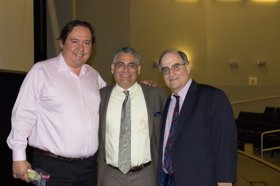 Three middle aged men in shirts, ties and blazers, stand side by side with arms around one another, smiling, in a large auditorium.