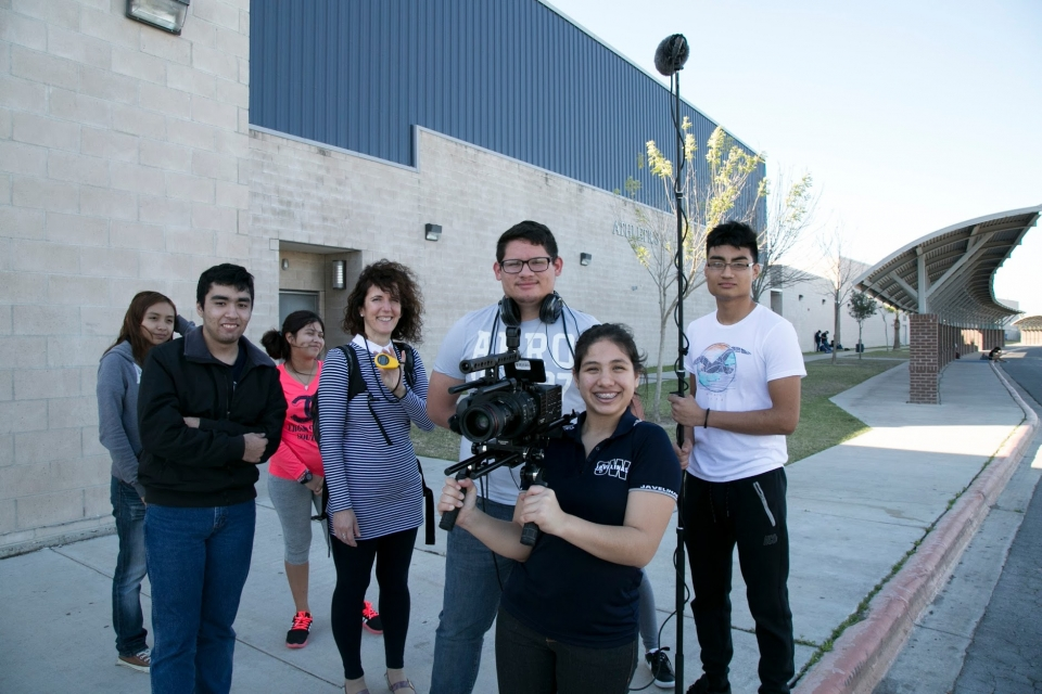 Seven high school students stand, smiling, on a sidewalk next to a large grey brick building, some holding audio-visual recording equipment.