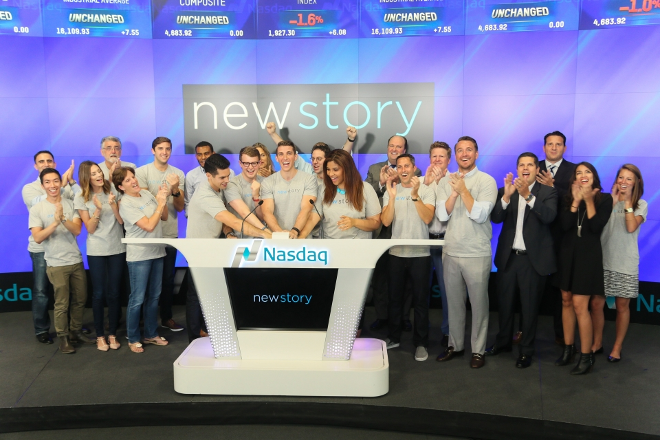 "A group of men and women stand behind a podium with NASDAQ written on it, cheering and clapping, while the screen behind them is displaying the words ""New Story"" on a blue background."