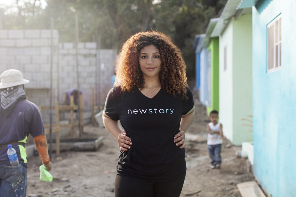 A woman in her thirties with long, curly brown hair, wearing a black t shirt and pants, standing with her hands on her hips, in an ally between houses being built, on a gravel road, with trees in the background,