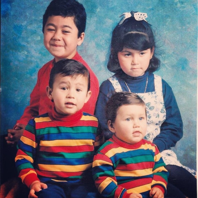 Portrait of four children: a boy in a red shirt, a girl in a blue shirt and flower dress, and two toddler boys on front in multi-colored striped shirts, in front of a textured blue background.