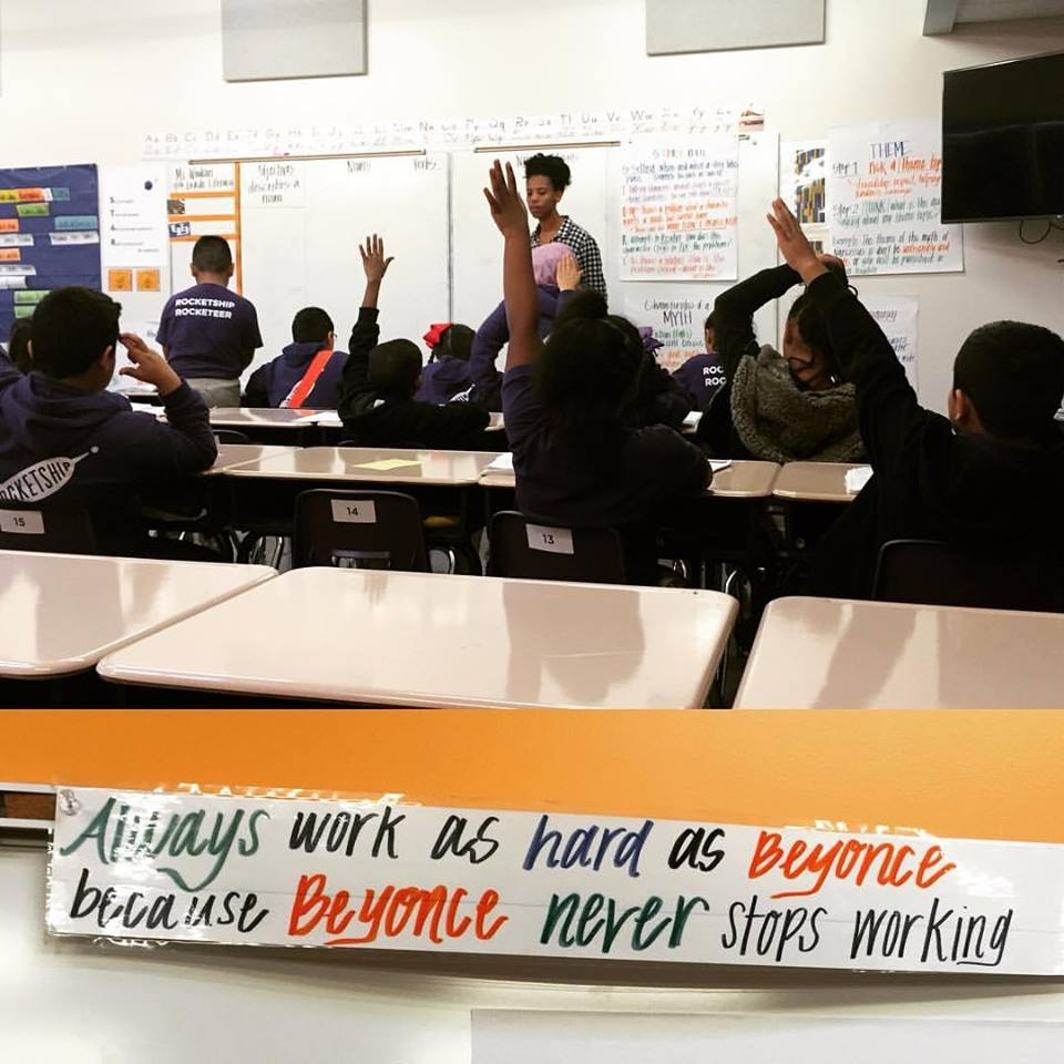 teacher in front of classroom with students raising hands