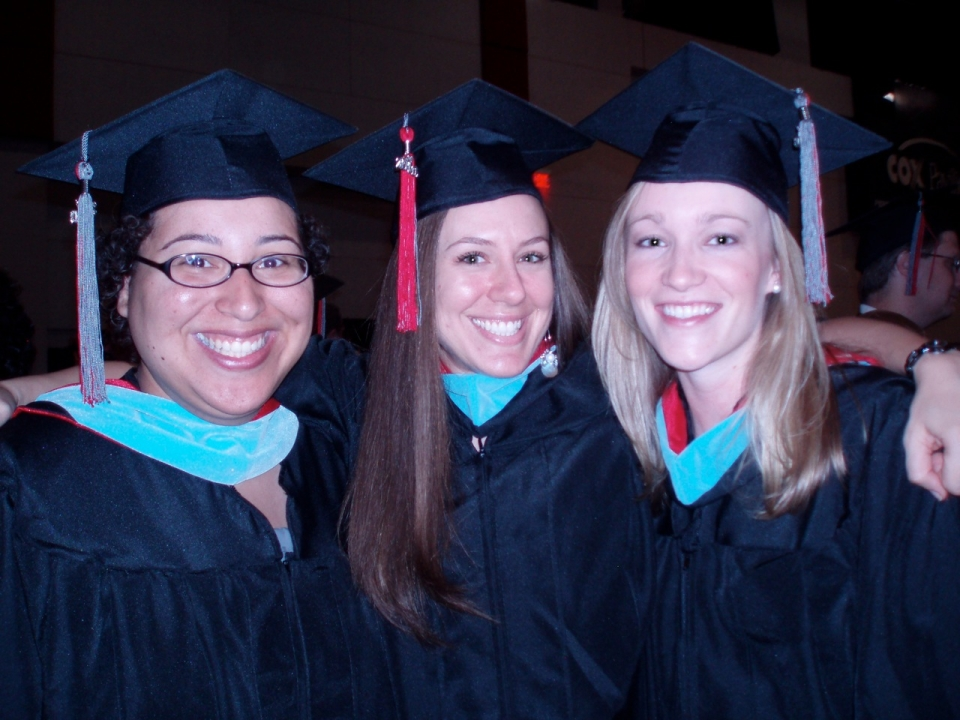 3 graduate school students in cap and gown after graduating